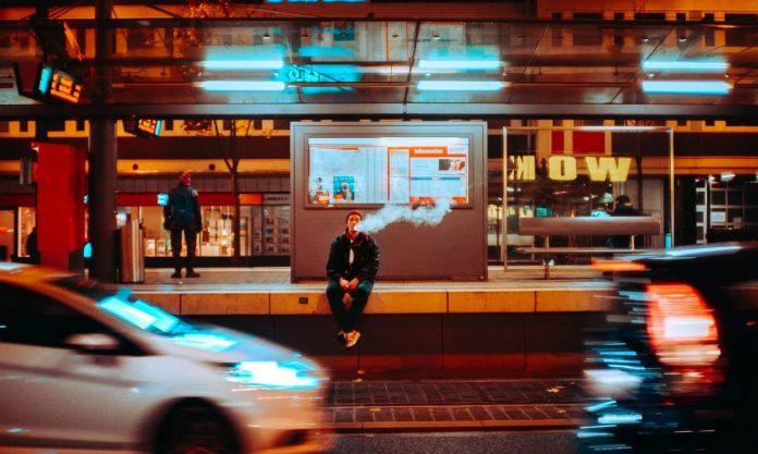 time lapse photography of man sitting on ledge smoking during night time